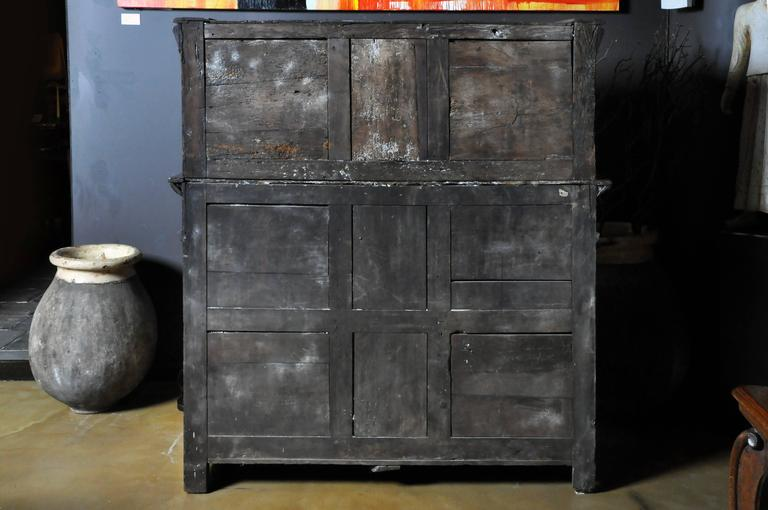 Hand-carved oakwood, 18th century, possibly earlier. Original finish throughout and no replacement or missing parts. Hardware is hand-forged iron. Marquetry decoration on door panels and crown. False drawers flank operable center drawer. All drawer