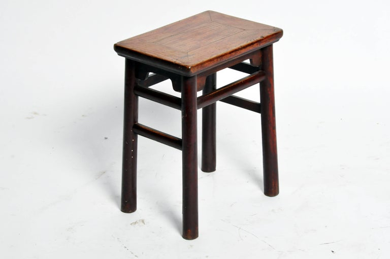 This handsome Qing dynasty Chinese stool is from Shandong, china and was made from elmwood. It features round posts designed, simple stretchers, and original lacquer.