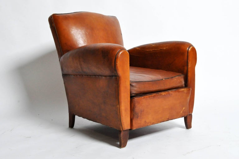 This handsome Art Deco leather chair is from Paris, France and was made from leather, c. 1940. The chair features its original leather, piping, and a beautifully aged patina.   Additional dimensions: 20