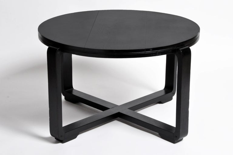 This British Colonial Art Deco round tea table is from Yangon and was made from teak wood, circa 1940. It features a new black lacquer finish with intersecting legs forming an