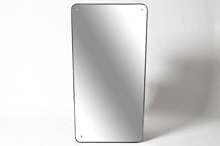 The large, tapered rectangular mirror plate has rounded edges and is outlined by a thin black wooden frame.