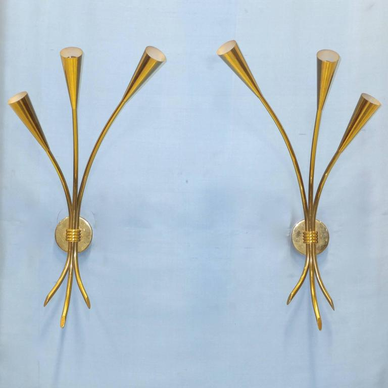 Pair of 1950s solid brass three-arm sconces by Lunel, model 701/3. In the form of a three stem bouquet of tulips with solid brass cones which taper evenly to the stem. Round brass backplate with signature Lunel four band brass ring clutching the