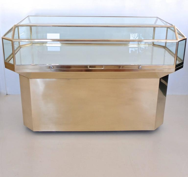 Matched pair of custom display cases in solid brass and glass with faceted emerald cut brass framed glass top attached to a recessed brass clad hexagonal pedestal base, finished in the round for 360 degree viewing. The top has two locks on either