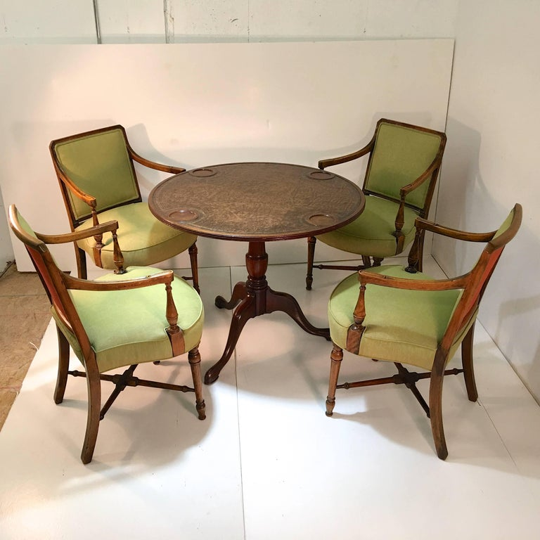 This round Sheraton style gaming table with leather top and four arm chairs were originally commissioned in the mid-1960s by top Boston interior decorator, George Clark, on behalf of a prominent family, from Florian Papp in New York City. The