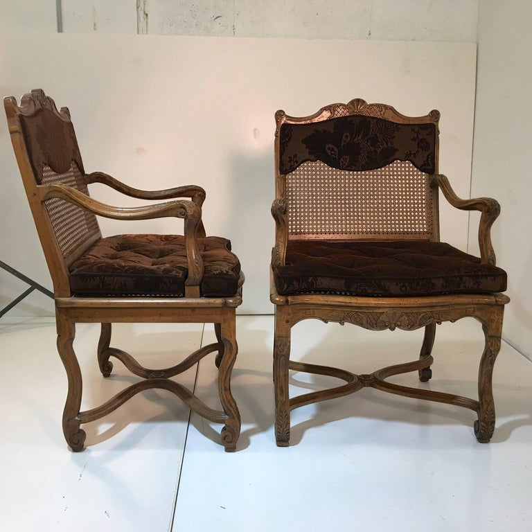 Set of ten dining armchairs carved by Don Ruseau Inc., New York City. Provincial Louis XV style with caned backs and seats. Fitted with custom seat cushions in brown cut velvet. These chairs were originally purchased by top Boston interior decorator