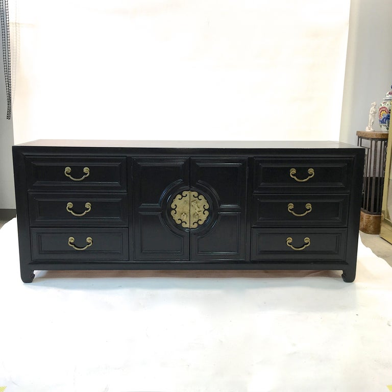 Vintage 1960s black painted nine-drawer chest of drawers by Century Furniture with solid brass hardware. Three drawers on left and right plus another three drawers behind the central double doors, with oriental motif hardware and mouldings.