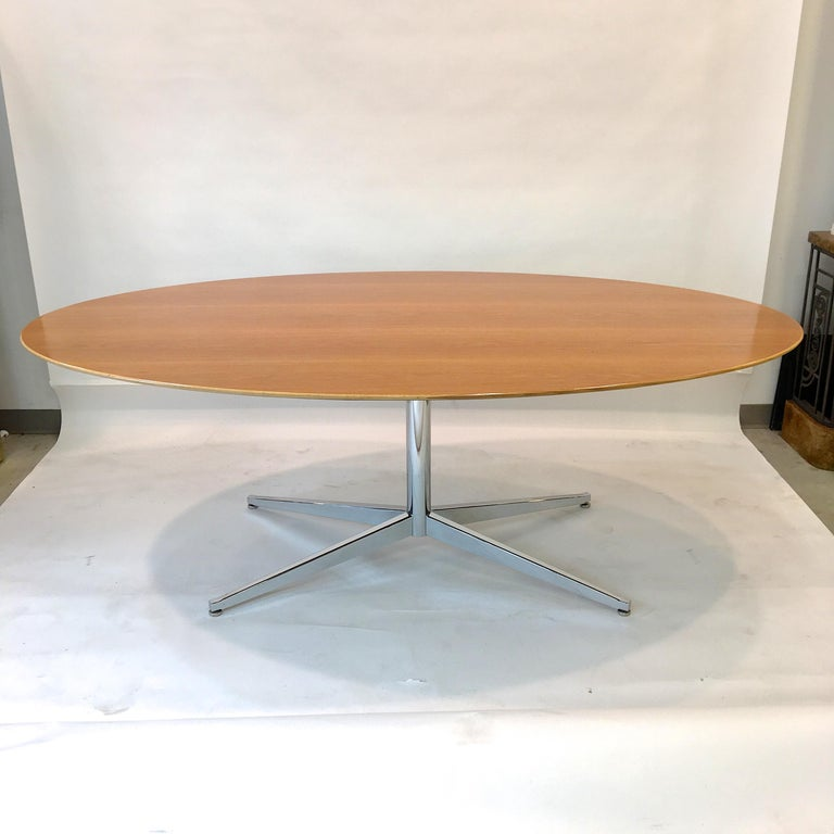 Original vintage Florence Knoll elliptical oval dining table or desk in oakwood with beveled edge on polished chromed steel pedestal and four star X base.
