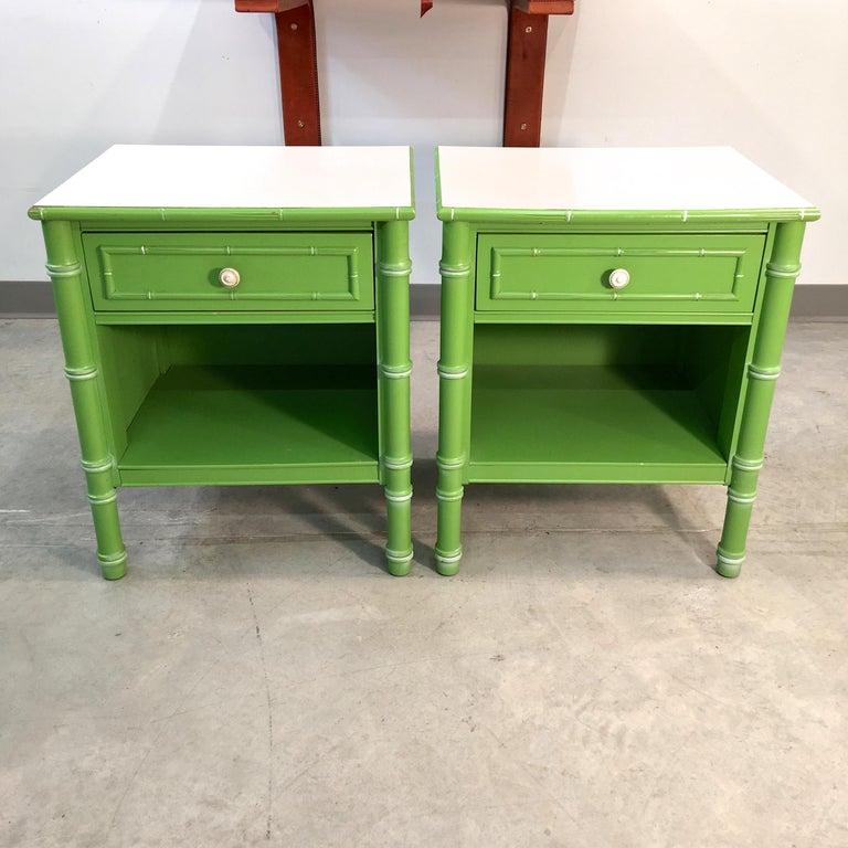 Pair of 1960s Thomasville Allegro faux bamboo nightstands in their original preppy pistachio green with striated white Formica tops. Each has a single drawer and an open storage space. They're closed off on the back.