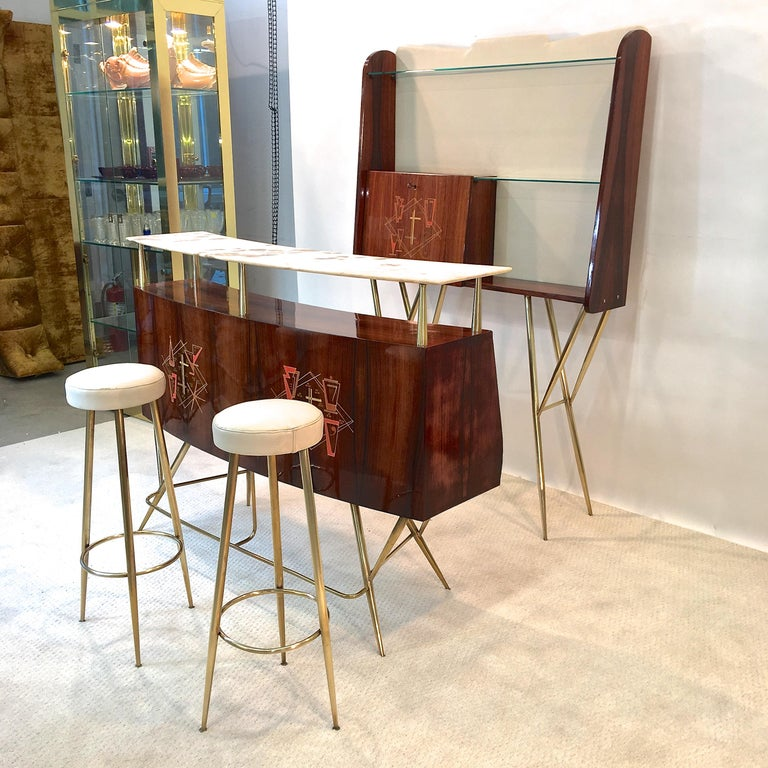 Exquisitely stylish 1950s Italian dry bar in rosewood and architectural tapered brass supports with floating curved marble top above a curved rosewood case inlayed with period cocktail motif graphic, open bottle storage on the backside and a single