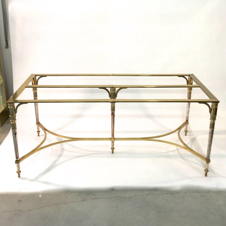 Incredibly well made neoclassical style rectangular five leg dining table made of solid brass and polished steel. The legs are tapered and are made of solid brass and polished steel. The cross stretchers are solid brass square bar. The top frame