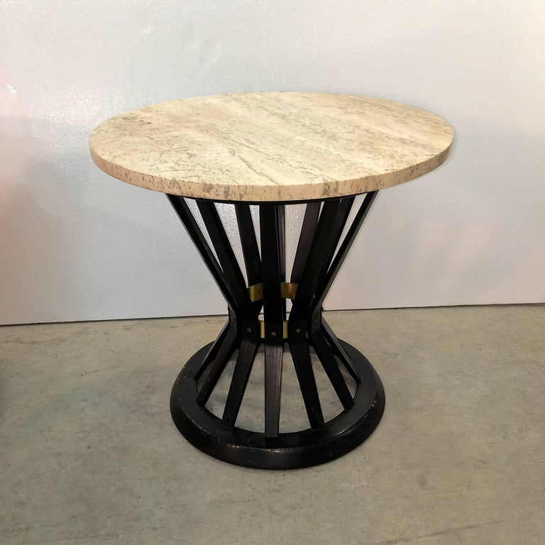 Travertine top round occasional table in the hourglass form of a bound sheaf of wheat with solid brass internal corset band with all original solid brass flat head screws. Original Dunbar metal tag present. Wood stain is original dark mahogany or
