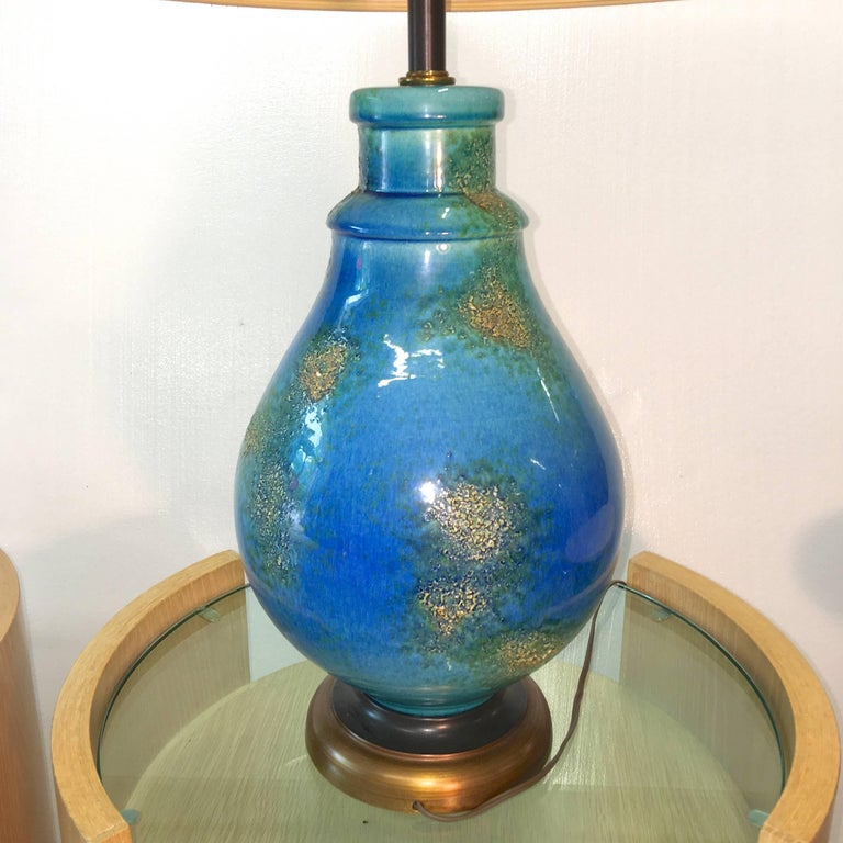 Glazed blue textured ceramic lamp, circa 1958. Great color and form.   If requested we can ship with the original drum shade which had a blue ribbon band.  Blue ceramic vase is 10 inches diameter.  21 inches high to the base of the bulb