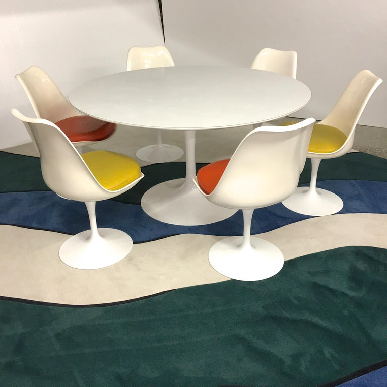 Restored vintage early 1960s Knoll production Eero Saarinen Tulip dining set with 54 inch diameter round white laminate tabletop and six tulip side chairs.  All aluminum tulip bases have been newly powder coated in high gloss white and look