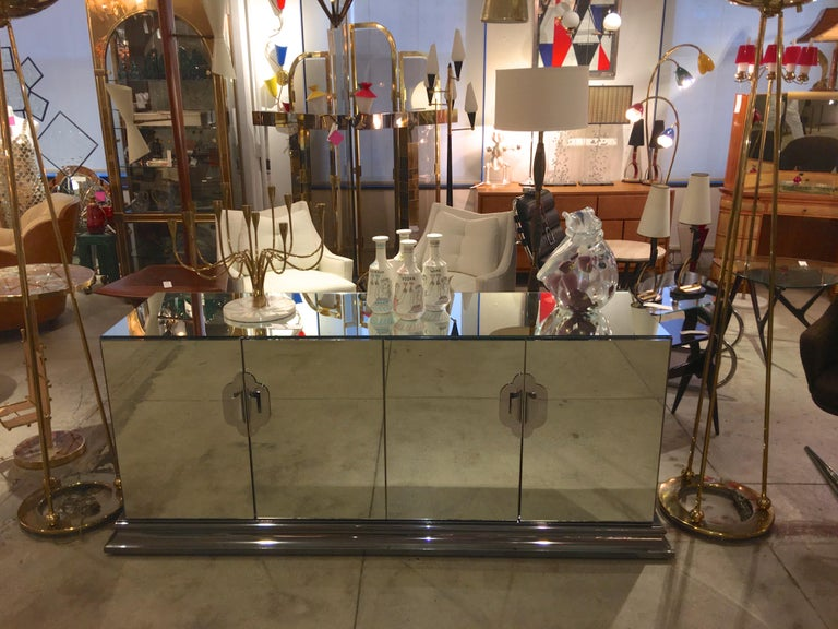 Luxuriously well constructed mirrored sideboard cabinet on heavy molded chrome plinth base produced by Ello Furniture Manufacturing Co. in the 1970s and designed by O. B. Solie. Materials used are mirror-polished stainless steel and laminated