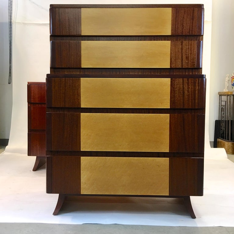 American Art Deco highboy dresser with Machine-Age lines in its tiered appearance and curved edge drawers. Produced circa 1947 by R-Way Furniture Co in the manner of Eliel Saarinen. Two tone bookmatched mahogany with exotic burl or curly maple inlay