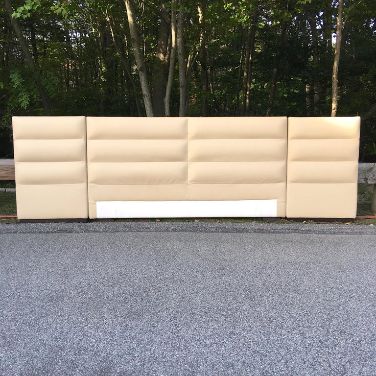 Opulent Fendi Casa light beige Italian leather upholstered king-size headboard and integrated nightstands. Excellent condition.  Headboard is three upholstered leather sections, each on ebonized ash bases and have Fendi logo dust cover on verso