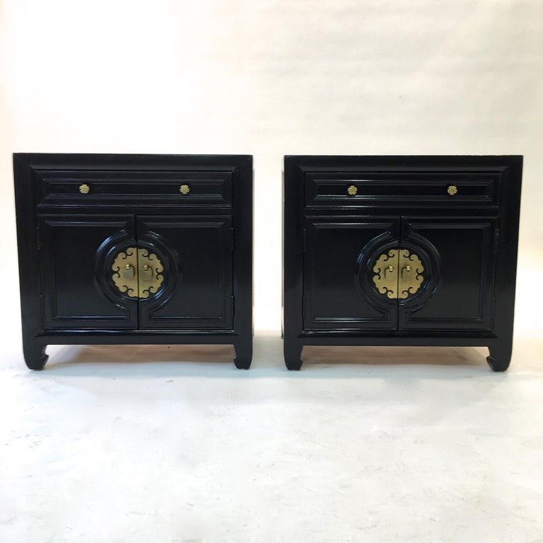 Vintage 1960s black painted pair of nightstands by Century Furniture with solid brass hardware and central oriental motif brass medallion. Two double doors below a single drawer with Century brand mark. The doors open to reveal an open compartment.