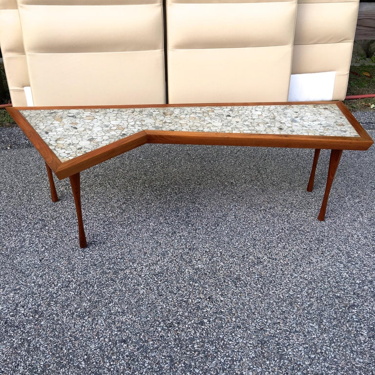 An artfully constructed walnut framed cocktail table in asymmetric rectangular form inset with irregular sized pebble shaped glazed stoneware tiles, standing on four organically turned walnut legs. Signed John Rothschild 1965.   Reminiscent of the