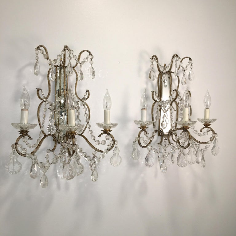 Pair of vintage Florentine beaded gilt metal and mirror framed three light sconces adorned with cut crystal garlands and drops. Wired for USA. Takes three candelabra size bulbs up to 250 watts per fixture.  Intended to be hard wired but can be