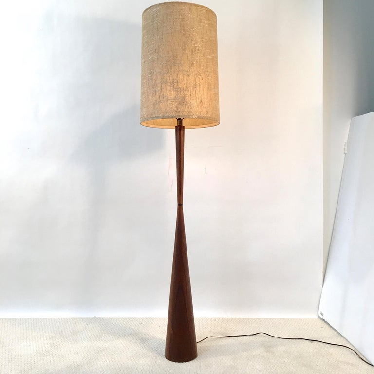 Walnut diabolo form floor lamp designed by Raymond Pfennig for Zina Lamp Co. in Northern California circa 1960. Original woven drum shade included.   46
