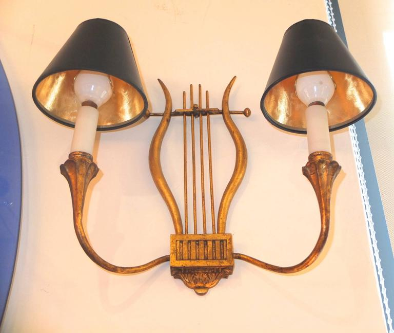Pair of gilt iron appliques in the form of a lyre created by Marc du Plantier for a private apartment in Madrid, 1940s. Two pair were created for this apartment, described as neoclassical Avant Garde modernist. We are fortunate to have this pair