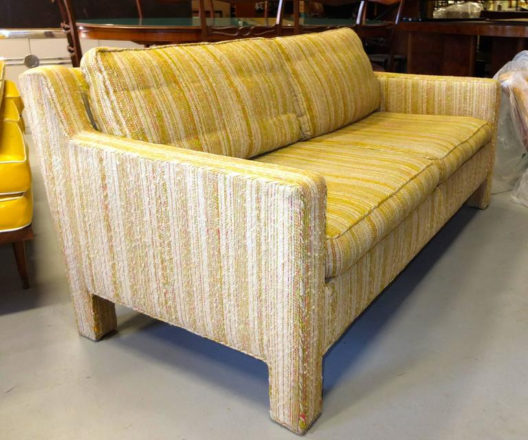 Chic early 1960's two cushion love seat sofa with original upholstery and original Dunbar decking, designed by Edward Wormley for Dunbar.  Two down filled loose back cushions.  Foam filled seat cushions.  Two sets of arm rest protectors.  Raised on