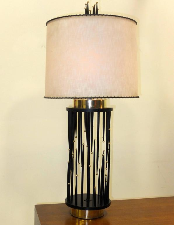Visually striking vintage 1960's table lamp with a cylindrical base composed of tapered black pointed spikes which are painted wooden dowels at irregular heights and each with a solid brass ball on its tip.  Brass recessed drum base and top and a