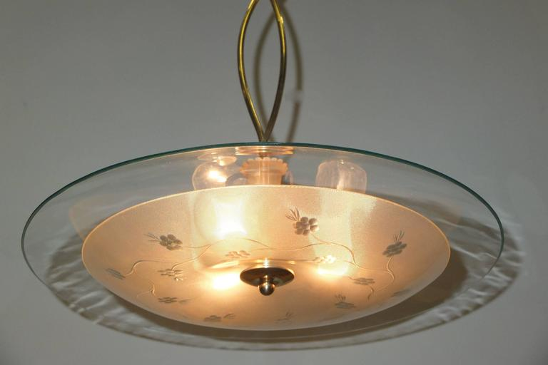 Gorgeous early 1950's Italian chandelier in the manner of Pietro Chiesa and Max Ingrand of Fontana Arte in the form of a flying saucer with clear crystal top and textured glass venturi shaped bowl with subtle etched flowers.  Most unusual is the