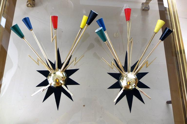 Spectacular custom made for the Casino de Clichy in France, a pair of wall mounted sputnik sconces each with five solid brass arms tipped with color enameled aluminum cones radiating from the top of a solid brass half sphere and solid brass
