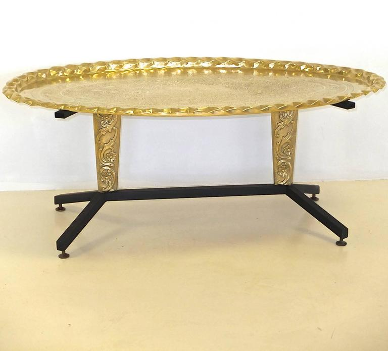 1960s Italian cocktail table with splayed black enameled steel legs and two moulded brass cartouche form pedestals above which are splayed steel supports. 