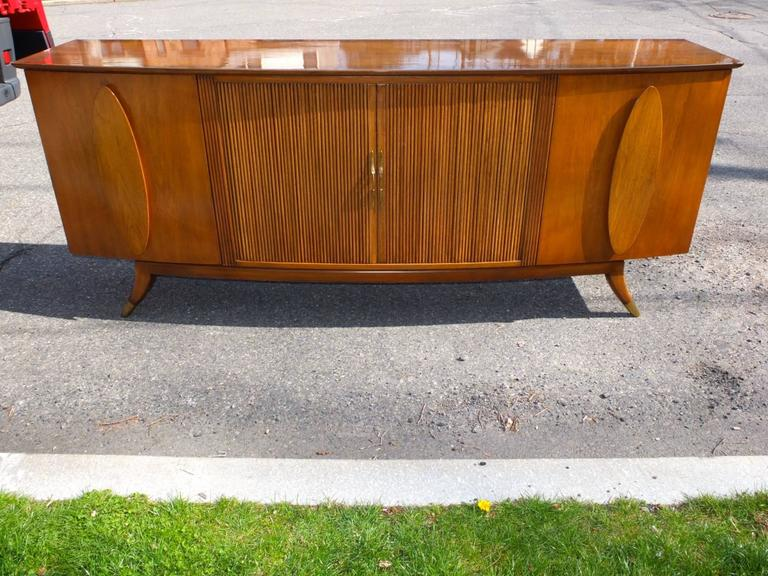 SATURDAY SALE  Long bow-fronted credenza sideboard in walnut with two cabinet doors and four drawers behind sliding tambour doors with brass pulls. The top two drawers are lined and divided for silverware. The two side cabinets each have two