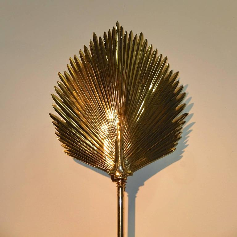 Unusual wall-mounted brass floor lamp in the style of Tommaso Barbi. Atop a long brass faux bamboo stem sits a large leaf-form brass reflector which is mounted to the wall by a rectangular brass backplate with a standard size Edison screw cap