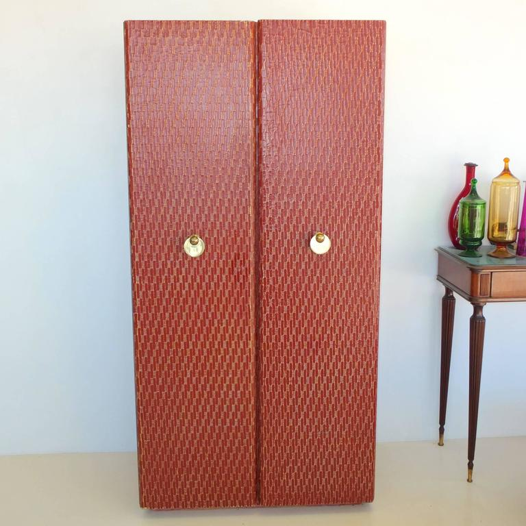 Nearly six foot standing bar cabinet wrapped in a textured cloth sealed in a dark red finish with two full length doors which open to reveal three levels the bottom for bottle storage the middle compartment, red lacquered and mirror-backed above a