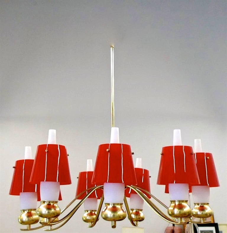 Ddesigned by Angelo Lelli and produced by Arredoluce Monza in 1959. Nine scrolled brass arms with brass bun shaped lamp holders with original white opaline glass chimney shades, further embellished by original flared plexi acrylic shades which slip