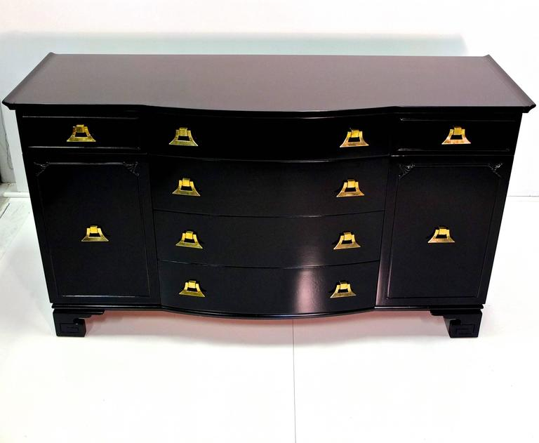 Pagoda form sideboard buffet in the style of James Mont with ming shaped feet and Asian motif detailing from the Exotic Modernist movement of the late 1940s-early 1950s, including distinctive solid brass decorative pulls. Freshly restored black