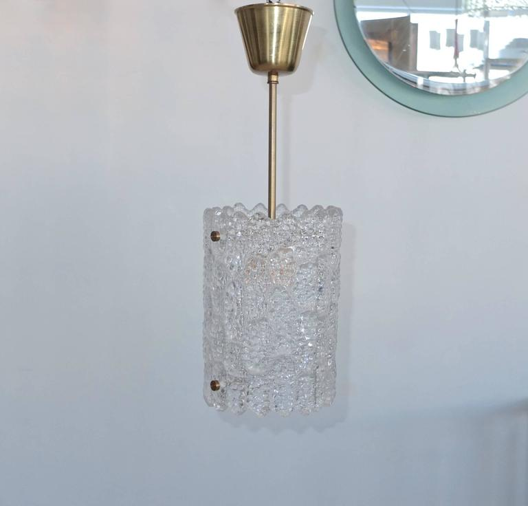 A Swedish crystal pendant light with brass hardware by Carl Fagerlund for Orrefors, Sweden. Late 1940s-early 1950s.  Total height including canopy is 20 inches. Glass only is 10 inches high by 7 inches diameter.  Takes a single standard size