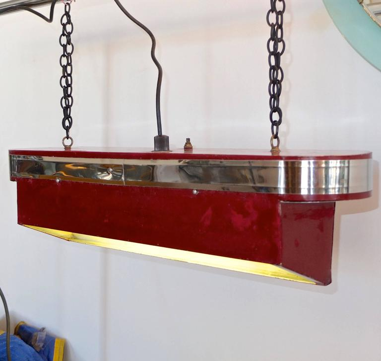 Streamline Art Deco horizontal hanging light with 17 inch fluorescent tube light. Stylish machine age oblong top reminiscent of a transatlantic ocean liner with chrome banding above wedge form steel box painted burgundy red. On or off switch on top