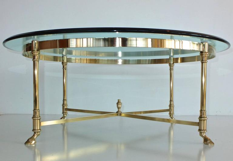 Round brass framed neoclassical style cocktail table in the manner of Maison Jansen. Four round legs standing on four cloven hoof feet braced by cross stretchers embellished at their intersection with an urn finial, and a mirror-polished brass ring