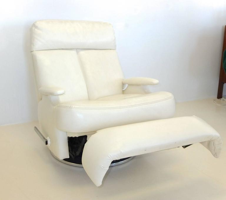 Upgrade to First Class at home (or at sea) with this pair of white kid glove faux-leather reclining swivel lounge chairs on round chrome pedestal bases by The Barcalounger Company of Buffalo, NY.  Since these have such a stable and low center of