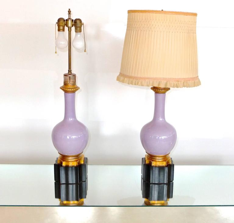 Truly beautiful pair of lamps. Lilac purple porcelain bottle form vases on ormolu mounts standing on octagonal black onyx base.  Brass double cluster lamping with adjustable height shade stem. On/Off by pull chain or cord switch.  These lamps were