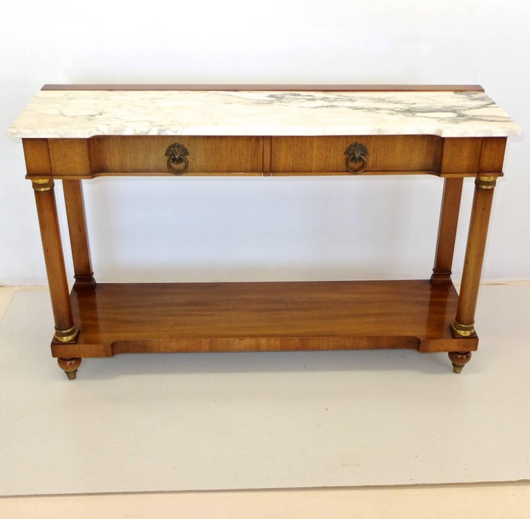 Empire style console table by John Widdicomb, circa 1960. Notched front edge white with black/gray marble top over two drawers having dovetail construction and brass ring pulls, supported by two turned columns with ormolu mounts and two flat colums