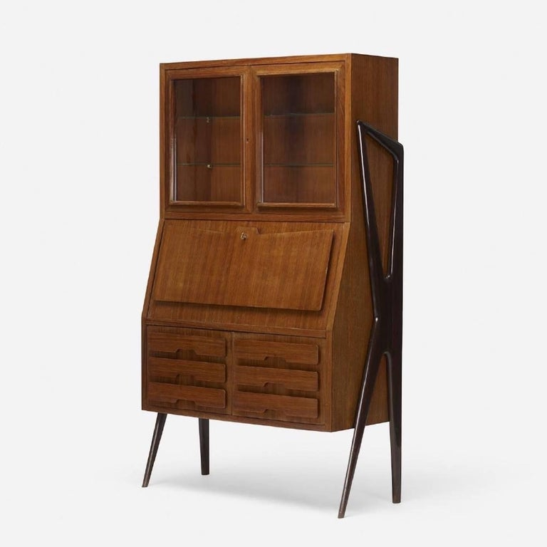 1950s Italian liquor bar cabinet or secretary writing desk book cabinet in lacquered rosewood with distinctive sculptural ebonized and scaffold-like legs. Pair of glass doors open to reveal two adjustable glass shelves. Drop front door with brass