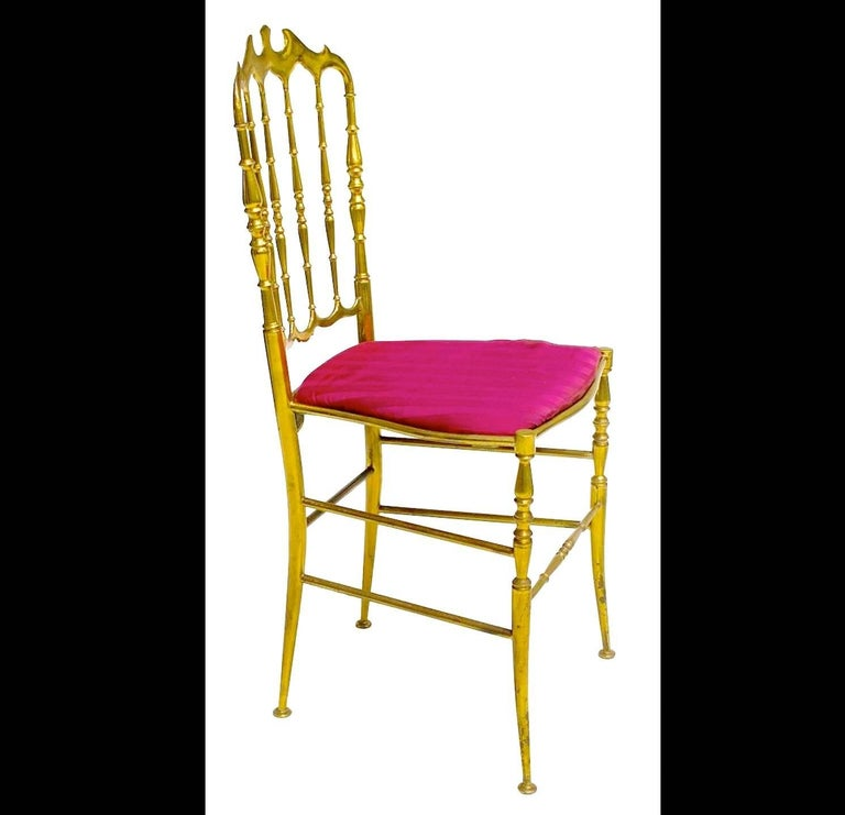 Pair of solid brass Chiavari ballroom chairs, Italy, c. 1960 with gilt brass frame, red upholstered seat, over tapered legs joined by brass stretchers.  This is the gold standard in chic! Solid polished brass 1960's Chiavari chairs with dainty splay