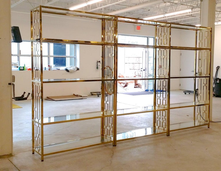 We currently have nine of these stunning custom fabricated brightly polished brass plated étagères each having five tempered clear glass inset shelves and distinctive geometric design grills on both ends. Each has four adjustable feet for leveling.