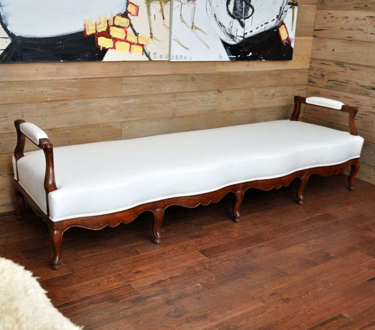 19th century French carved wood and upholstered bench Unusual French bench or daybed with gracefully curving front and straight back side. Newly upholstered and new cushion in white cotton muslin Measures: Arm height is 26