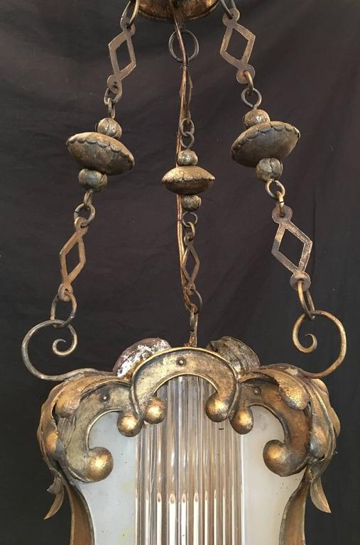 This Baroque lantern was made in Venice, Italy, during the 18th century, circa 1760, and features a gilded tole body covered in scrolls and floral design. The frosted glass center contains Venetian blown glass rods and was originally candle. It has