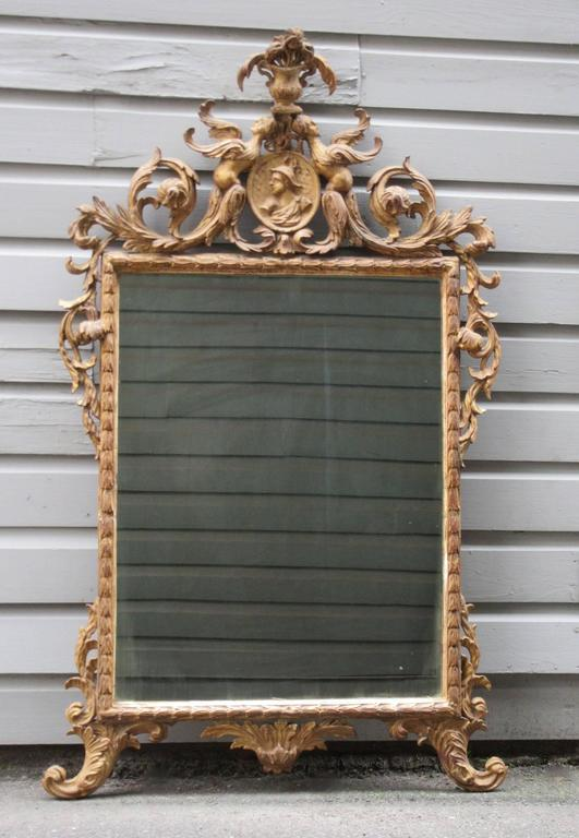 A stylish Italian Rococo carved giltwood mirror, circa 1780, in the Chinoiserie taste and featuring Venetian carved motifs.