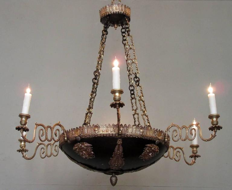 This dramatic chandelier was made in Italy in the late-18th century, circa 1780, and features a canopy bordered with acanthus leaves that has three supporting chains. The bowl of the chandelier is patinated bronze with applied bronze neoclassical