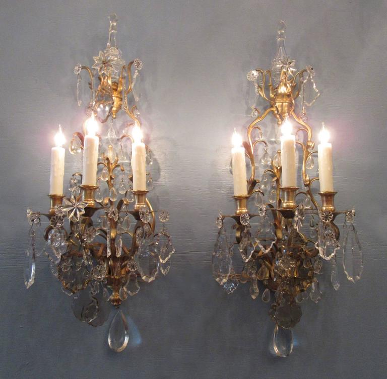 A large pair of 19th century French Louis XIV bronze doré and crystal sconces, circa 1830, each featuring three candle arms and large clear and smokey cut and polished crystal pendants. The pair have recently been cleaned and rewired with new