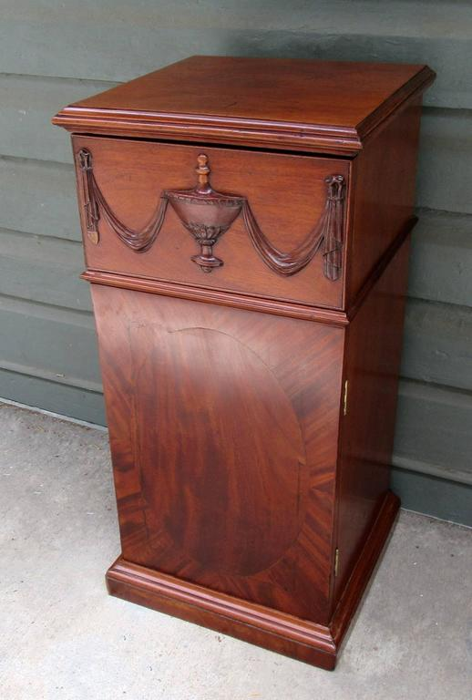 An early 19th century English Regency mahogany pedestal cabinet, circa 1810, featuring an urn with swag carved drawer and single cabinet door below.